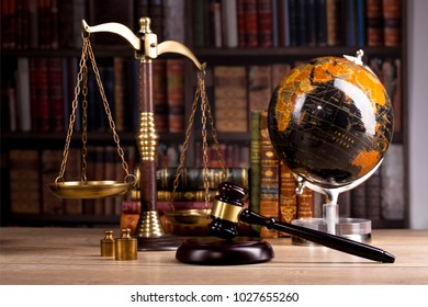 Vintage office room in a law firm with the scales of justice, legal hammer and an old globe on the table with law and codex books library in the background