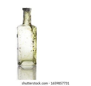 Vintage oil and tincture glass bottle weathered on white background. Old bottle with calcium deposits. Copy Space