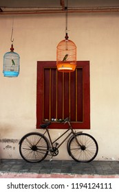 vintage old bicycle and two bird cages hang on ceiling of the old house of chinese-javanese style in ancient china town in Lasem, Central, Java Indonesia.