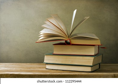 Vintage old books on wooden deck table and grunge background