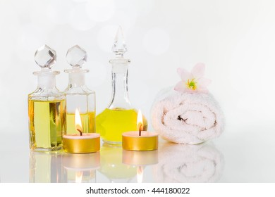 Vintage old bottles of aromatic oils with burned candles, flowers  and white towel on glossy white table on white background with bokeh, aromatherapy concept