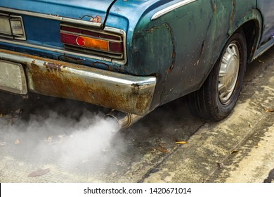 Vintage old car emits pollutant out of the exhaust