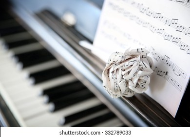 Vintage old classic piano with paper rose and musical notes on it, close up