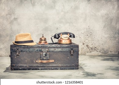 Vintage old classic travel trunk luggage with leather handles circa early 1900s, rotary telephone, hotel service bell and men's hat. Retro style filtered photo