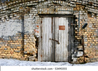 Vintage old door with brick wall. Front view of the entrace to abonded warehouse on the main street in center of Riga, Latvia.