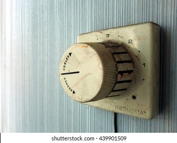 Vintage old grimy thermostat control on wall macro