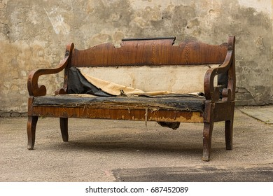 Vintage old grungy ripped abandoned couch, sofa let for garbage.