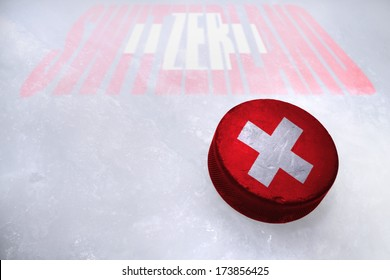 Vintage old hockey puck with the Switzerland flag is on the ice
