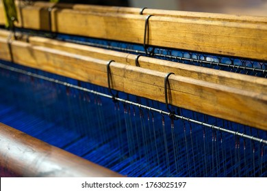 Vintage old loom weaving machine close up. Old Textile Machine. A loom machine for clothing or woven label. Yarn thread lines on the weaving loom machine for clothing  in textile or garment factory.