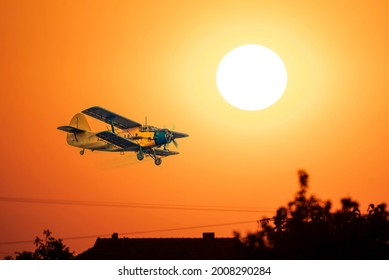 Vintage old plane flying low altitude during sunset sky    - Shutterstock ID 2008290284