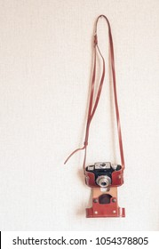 Vintage old rangefinder photo camera hanging on wall background. Vintage hipster theme color tone styles. Photography back to old school concept. Close up, copy space. Place for text.