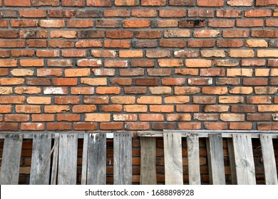a vintage old red brick wall with leaning weathered pallets