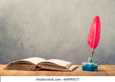 Vintage old red quill pen with inkwell and open book on wooden table front concrete wall background. Retro style filtered photo