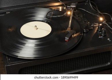 Vintage old retro vinyl electronic record player with black record and cartridge needle installed close up