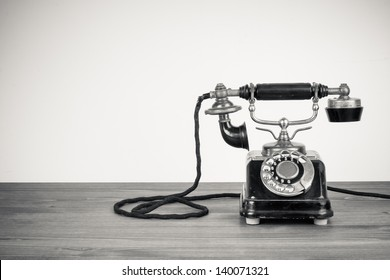 Vintage old telephone on wood table black and white photo