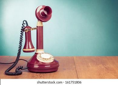 Vintage old telephone on wood table near aquamarine wall background