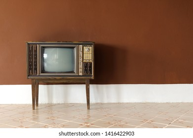 Vintage old television on wood table in brown room, Retro television technology.