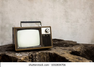 Vintage old television on the wooden with white wall background