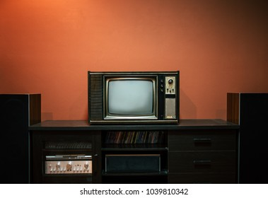 Vintage old television on wooden table in the room.