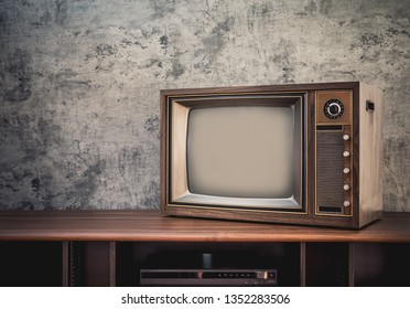 Vintage old television on wooden table in living room with concrete wall background.