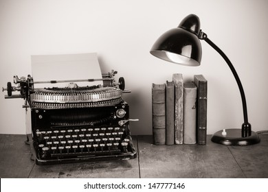 Vintage old typewriter, old books and retro lamp on table