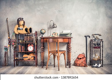 Vintage old typewriter, lamp, carnival mask, globe on antique table, chair, Teddy Bear with photo camera, retro clock, books, fiddle, keys on shelf, telephone, souvenirs, shoes, cane, backpack, bow