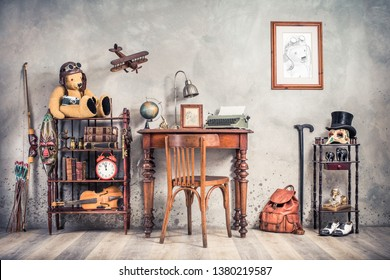 Vintage old typewriter, lamp, frame, forefinger on antique table, chair, Teddy Bear with photo camera, retro clock, books, fiddle, keys on shelf, plane, mask, cylinder hat, shoes, cane, backpack, bow