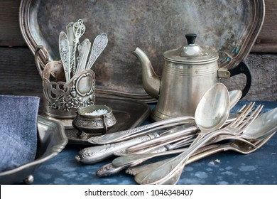 Vintage old utensils made of nickel silver, tableware (kettle, teaspoons, tablespoons, knives, forks, tray, dish), horizontal, space for text