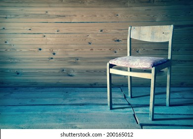 Vintage old wooden chair in grungy interior. Loneliness, estrangement, alienation concept. Toned image