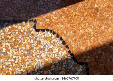 Vintage old-style Italian terrazzo flooring, narrow stripe of which is illuminated by a ray of sun. Light entering through the crack of a slightly open door. Arched passageway floor in Bologna, Italy.
