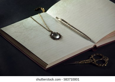 Vintage open book on a black background. vintage pendant on the pages of the old book