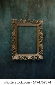 Vintage openwork bronze metal frame on a old wall background