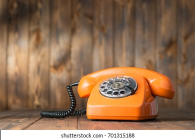 Vintage orange phone on a wooden table