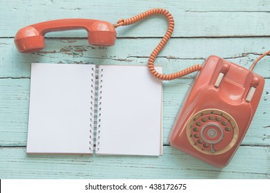 vintage orange-red telephone, notebook on wooden background close-up, top view, pick up the phone