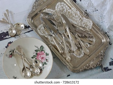 Vintage ornate silver cutlery flatware on a silver tray with lace napkins, china plate on a distressed wood table - dinner party