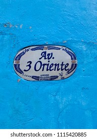 A vintage oval street name sign made of talavera, attached to a blue wall on the exterior of a historic building in Puebla, Mexico.