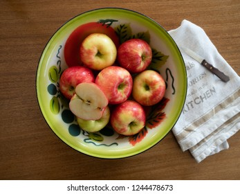 Vintage painted tin bowl with seven organic honeycrisp apples and a half an apple. A dish towel and paring knife are next to the bowl. Photographed from above on a wooden table.