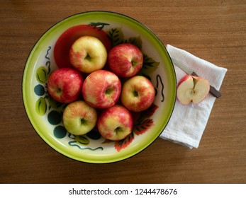 Vintage painted tin bowl with seven organic honeycrisp apples. A half an apple and paring knife are on a dish towel next to the bowl. Photographed from above on a wooden table.