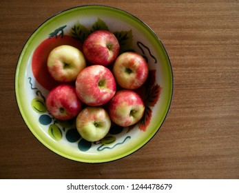 Vintage painted tin bowl with seven organic honeycrisp apples. Photographed from above on a wooden table. Copy space.