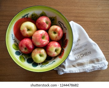 Vintage painted tin bowl with seven organic honeycrisp apples. Photographed from above on a wooden table with a dish towel. Copy space.