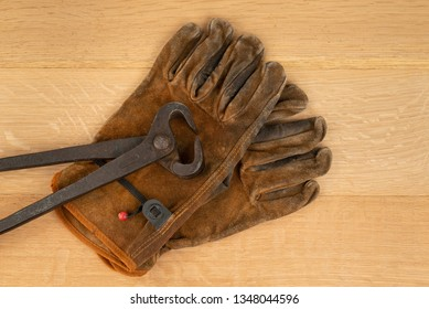 Vintage Pair Of Long Handle Cutting Pliers Nippers and well Worn Leather Work Gloves Wood Background