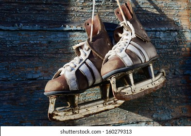 vintage pair of mens  ice skates hanging on a wooden wall