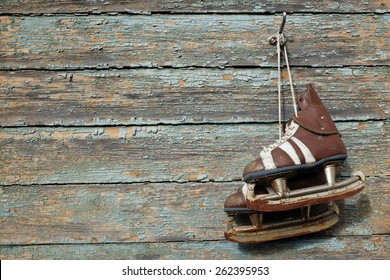vintage pair of mens  ice skates hanging on a cracked paint wall