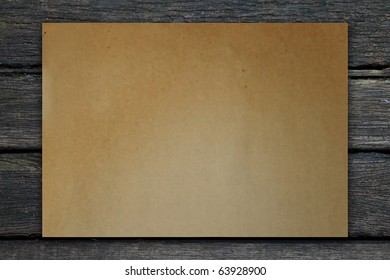 Vintage paper on old wooden plank background.