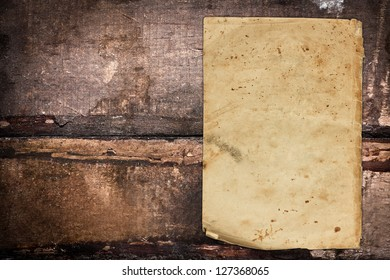 Vintage paper sheet on a grungy wooden background