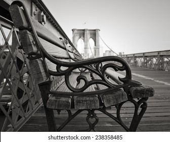 A vintage park bench on the Brooklyn Bridge facing Manhattan in black and white.