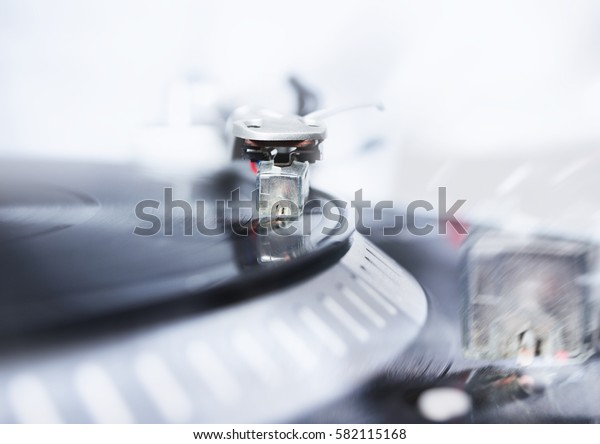 Vintage party dj turn table records player play old black analog vinyl disc with music.Hifi audio equipment.Retro dj technology to scratch records and mix tracks.Focus on turntables needle on a record