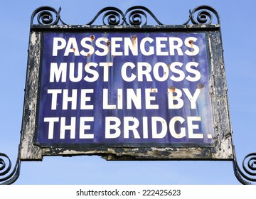 Vintage 'Passengers must cross the line by the bridge' railway sign.