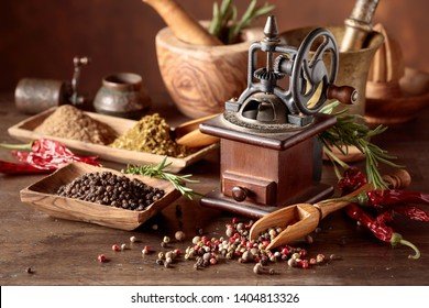 Vintage pepper mill with various peppers and spices. Old pepper mill with kitchen utensils, spices and rosemary on a wooden table.