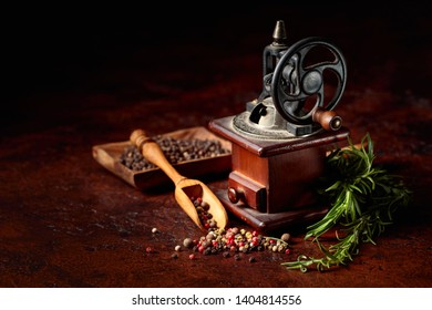 Vintage pepper mill with various peppers and spices. Old pepper mill with cooking utensils, spices and rosemary on a brown background.